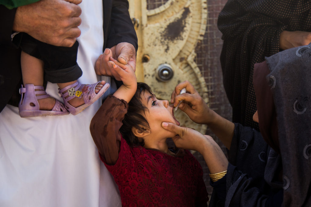 A girl receives a drop from an adult holding her mouth open.