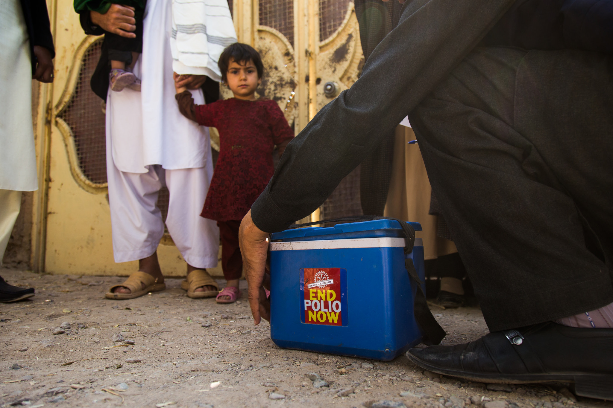 A child holding an adult's hand looks on at a man opening a box on the floor labeled: End Polio Now.
