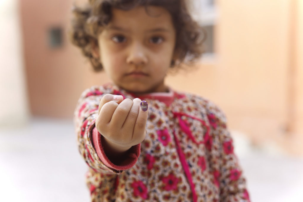 A child with a painted finger outstretched.