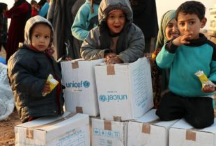 Children sitting atop white cardboxes boxes.