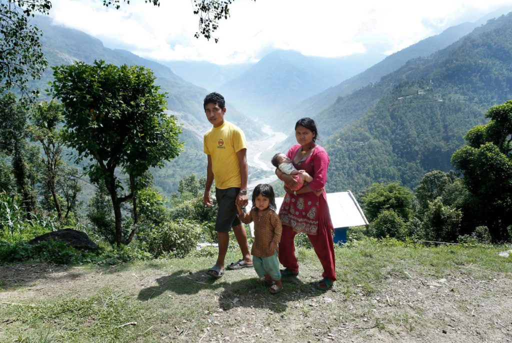 A young couple walk along the hillside with their children - a girl walking alongside and a baby in the mother's arms.