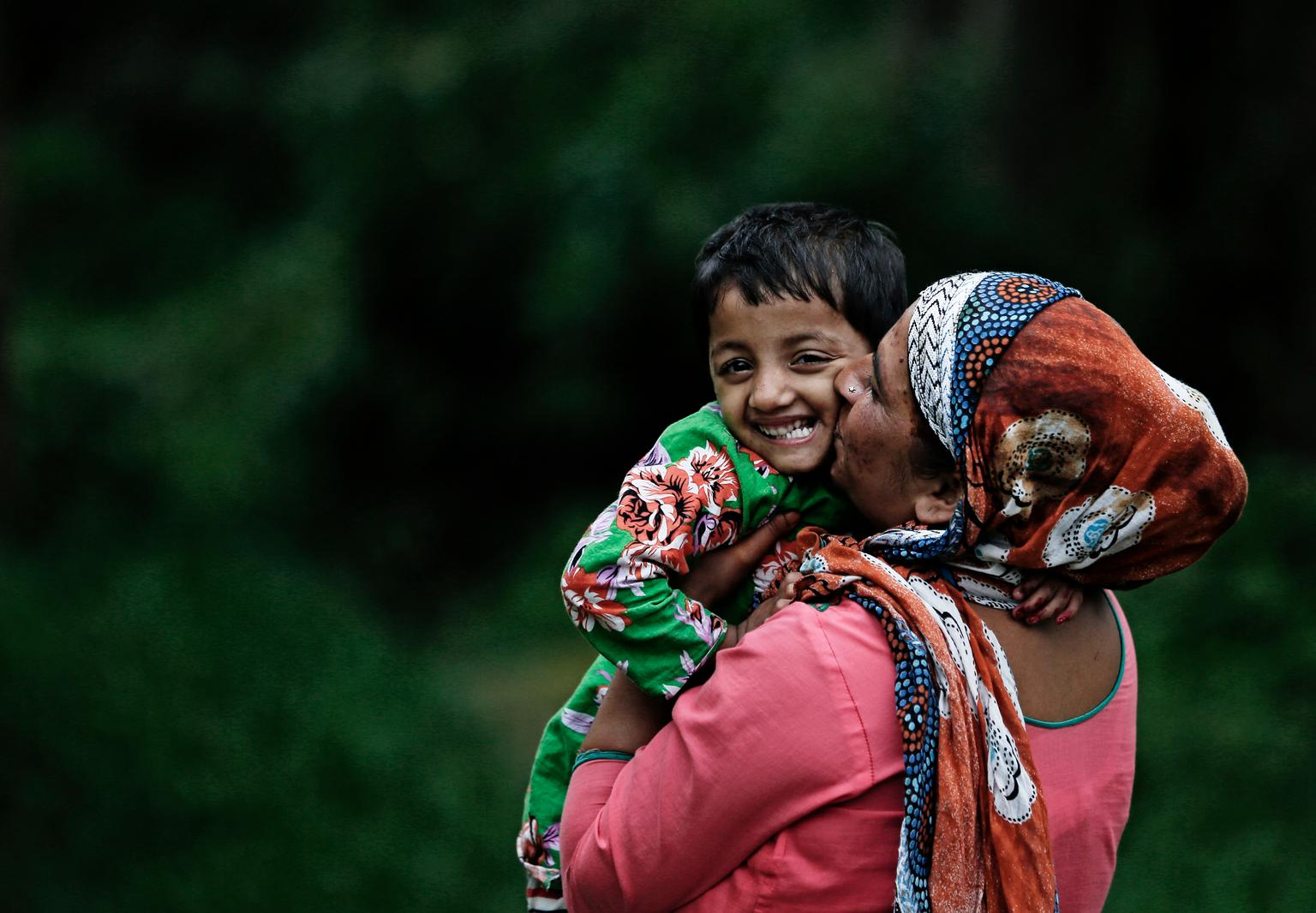 A woman kisses the child she has held in her arms.