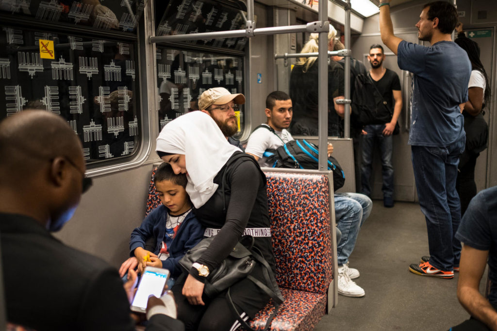 A woman in a headscarf holds her child as they sit in a subway car carrying other passengers.