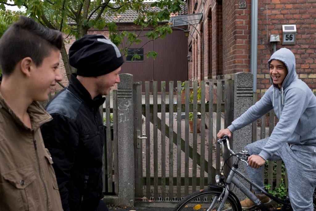 Two young boys meet and greet with another on a bicycle on the street.