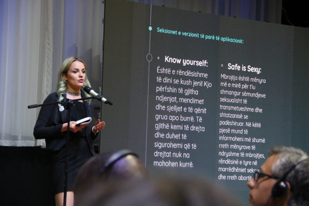 A young lady addresses an audience over a mic, with a display screen behind with text in Albanian and English: 'Know yourself' and 'Safe is Sexy'.