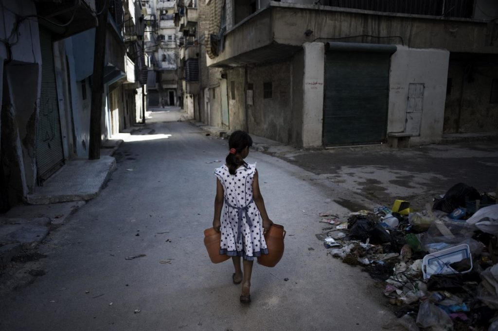 A girl carrying a jerry can in each hand walks on a deserted street.