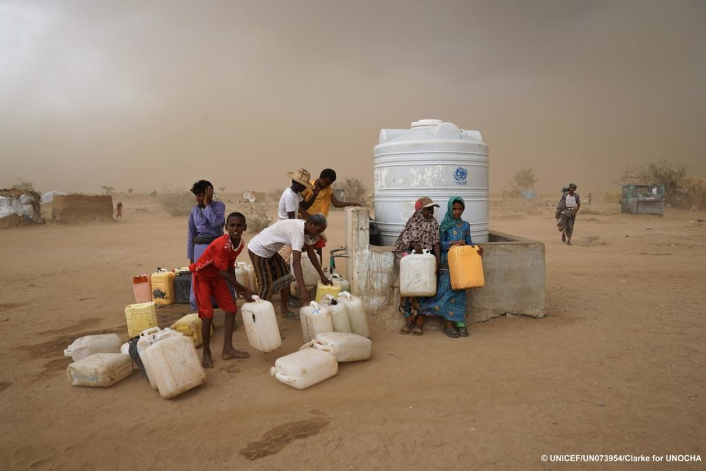 A group of people in a windy desert manage jerry cans in front of a large water container.
