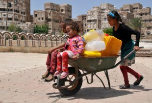 A girl pushes two younger children in a wheelbarrow that also bears several jerrycans