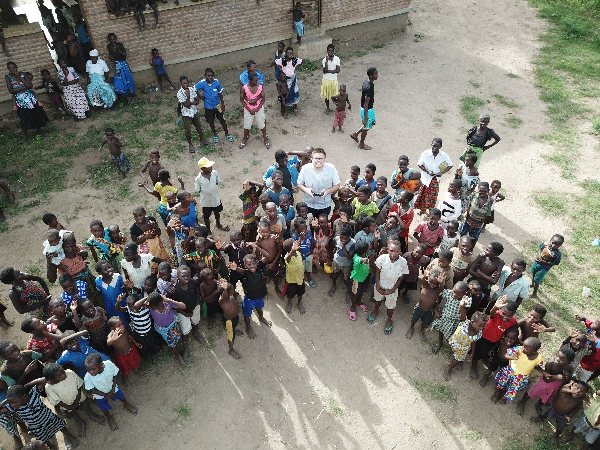 Aerial view of a drone operator surrounded by children