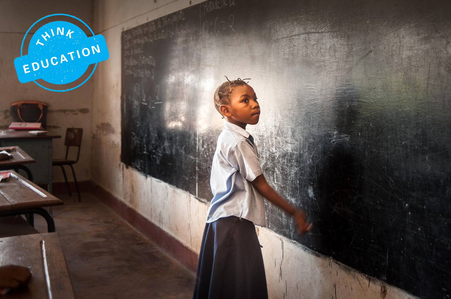 A young girl reaches out towards the blackboard in a classroom.