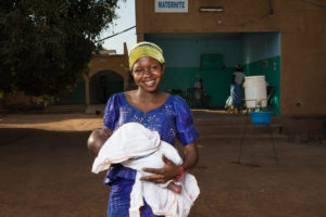 A lady cradles a swaddled baby in her arms.