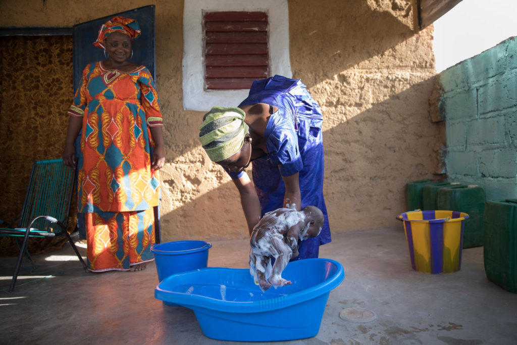 A lady halding a soaped baby over a blue bathing tub, as a woman looks on.