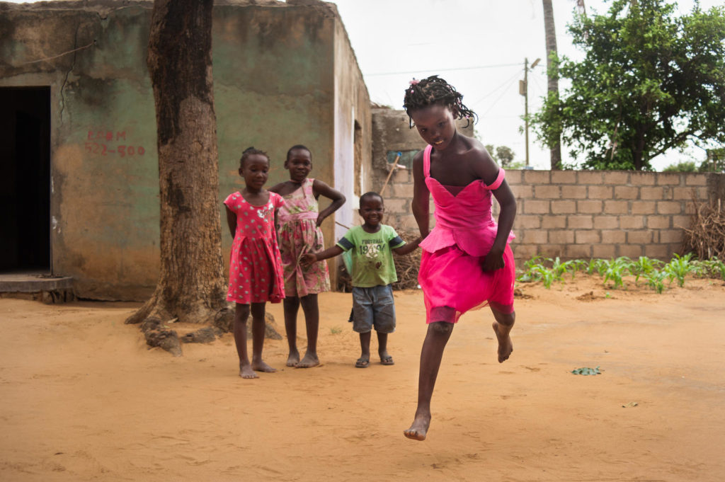 A young girl in midair as she jumps while playing as some children look on.