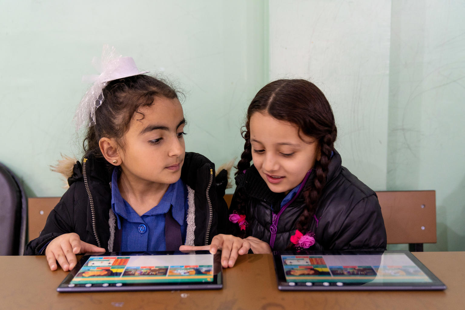 Two young schools girls with tablet PCs at a desk.