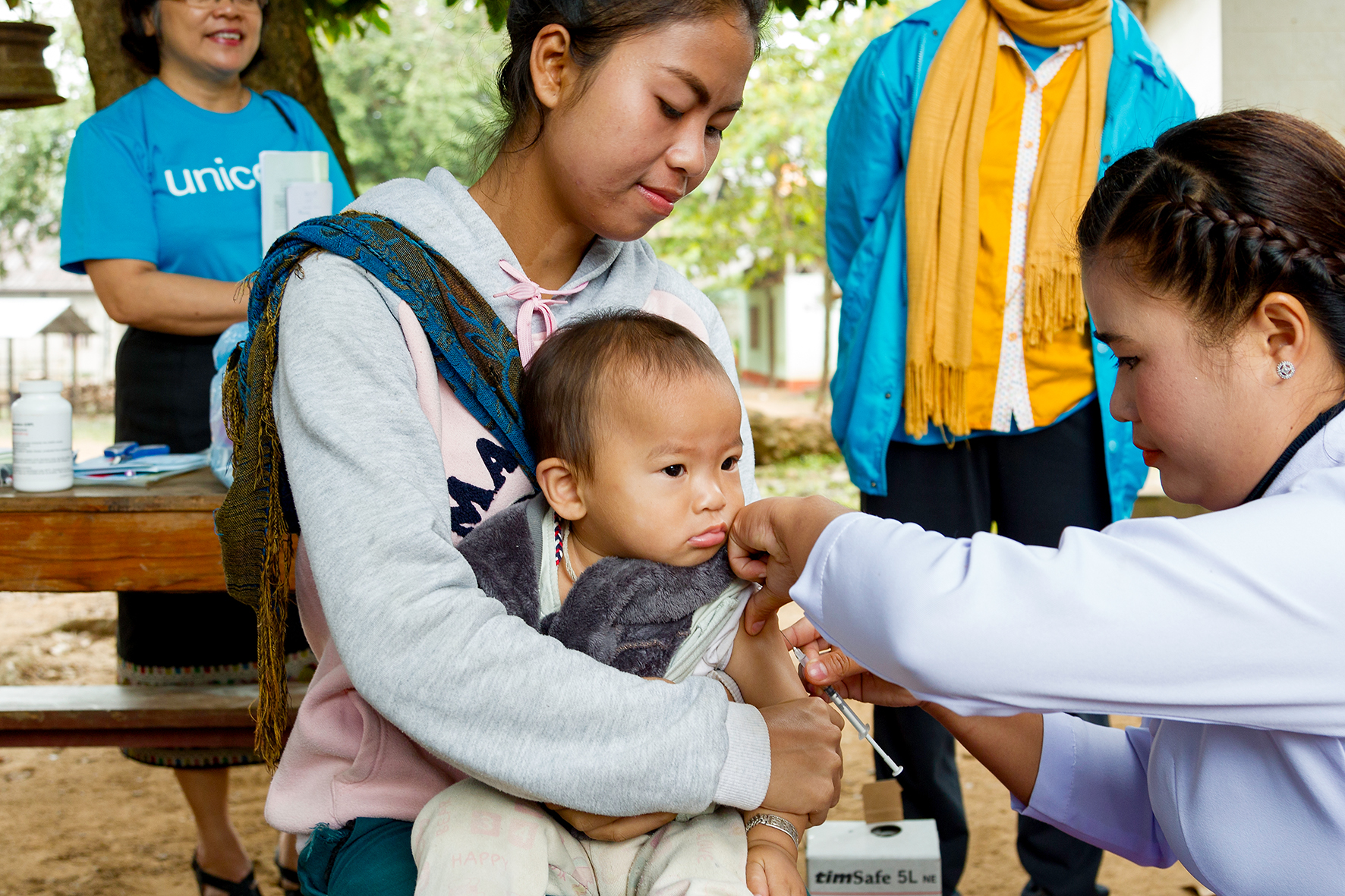 A lady administers a vaccine on a baby held by another lady.