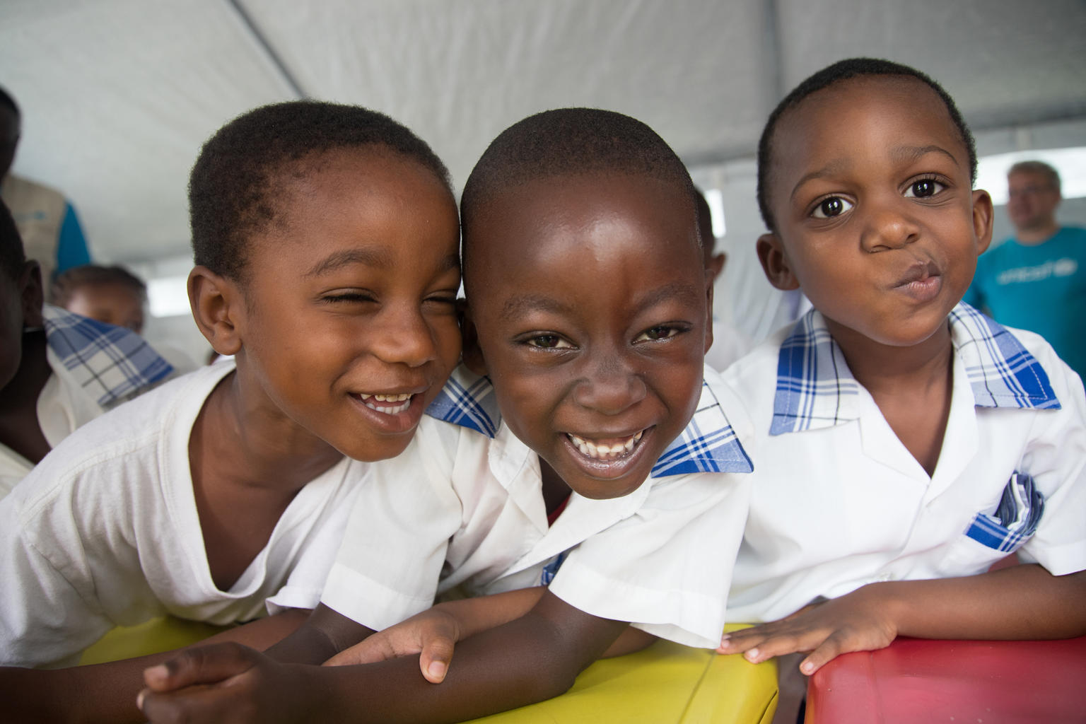 Three school children smiling closely at the camera.