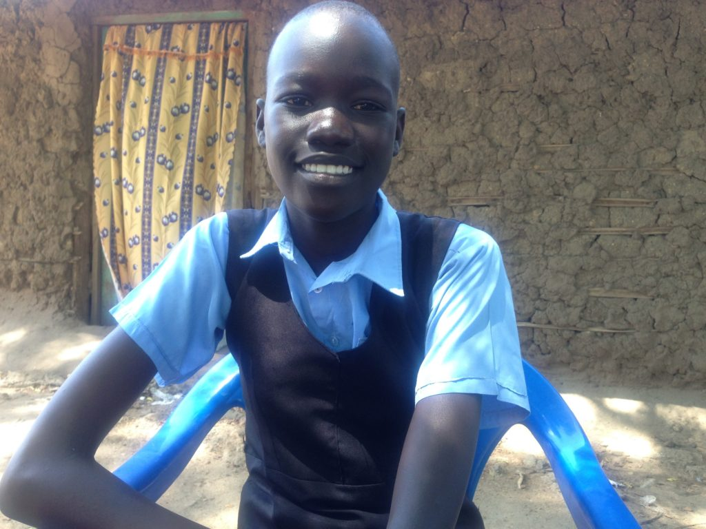 A girl in school uniform sitting on a blue plastic chair.