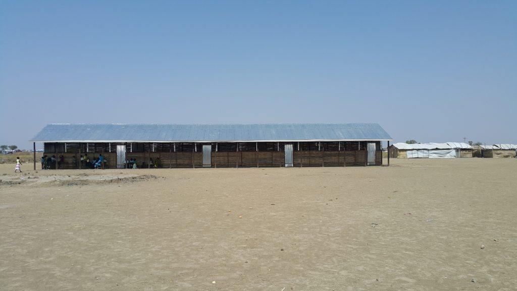 A horizontal tin-roof building in a barren field.