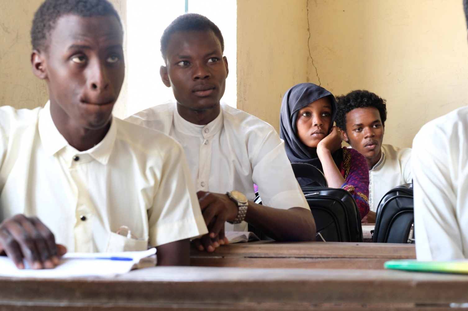 A row of young boys and a girl sitting one behind another in a classroom.