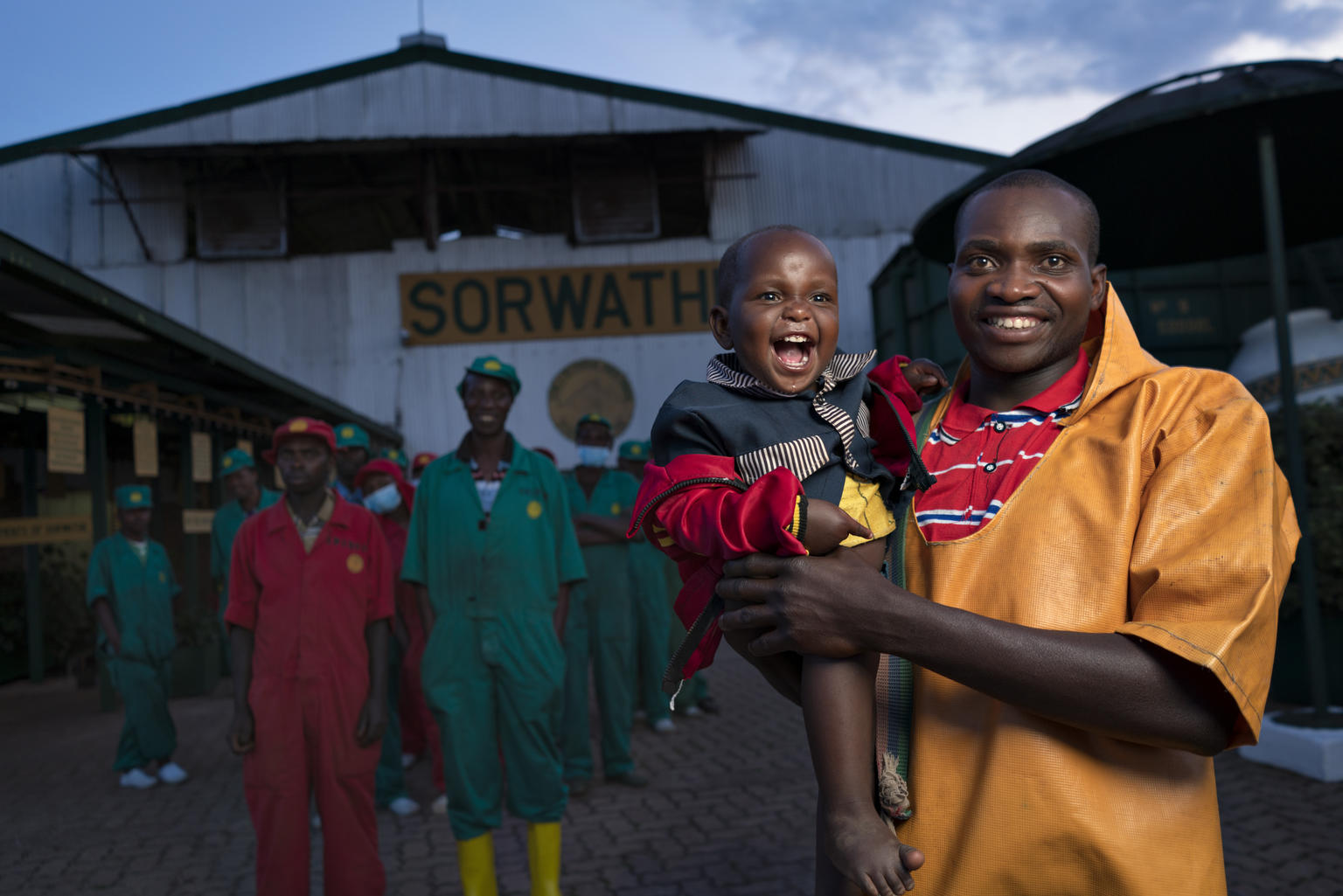 A man in factory clothes holds a smiling child as some other workers look on