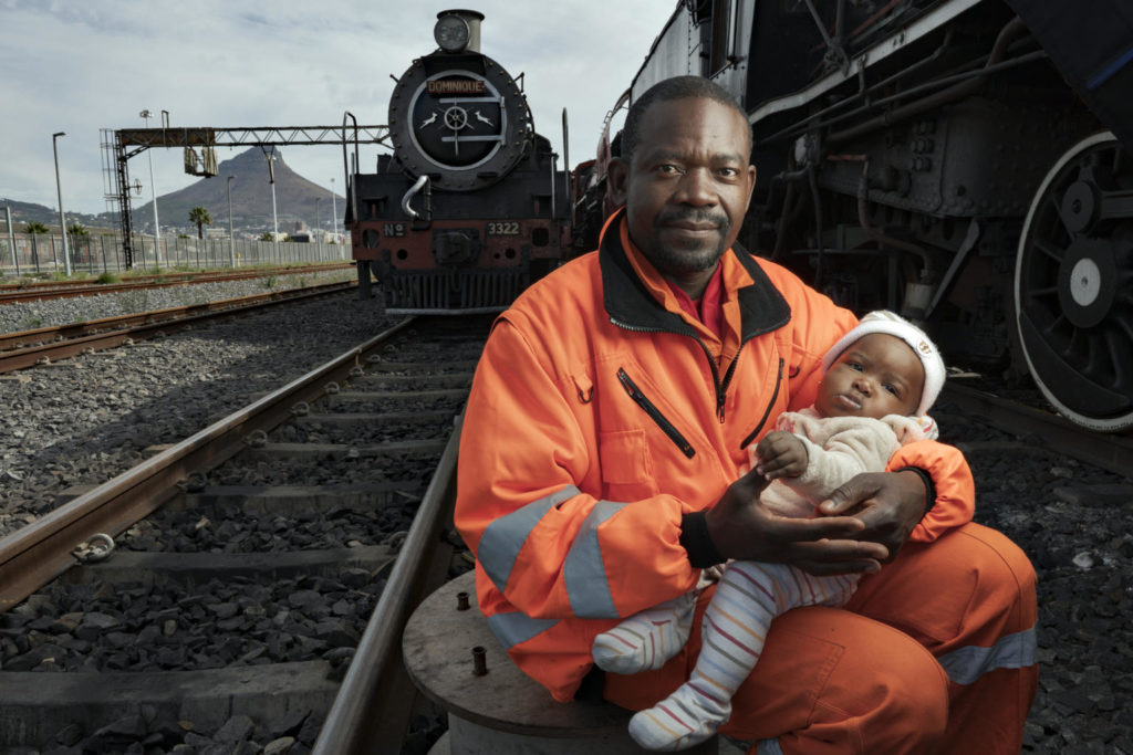 A father sitting besides railway tracks holds an infant