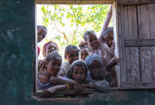 Children peeking into a room through an open window