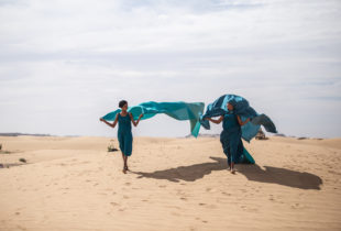 Two ladies in blue flowing garb walk across desert sands.
