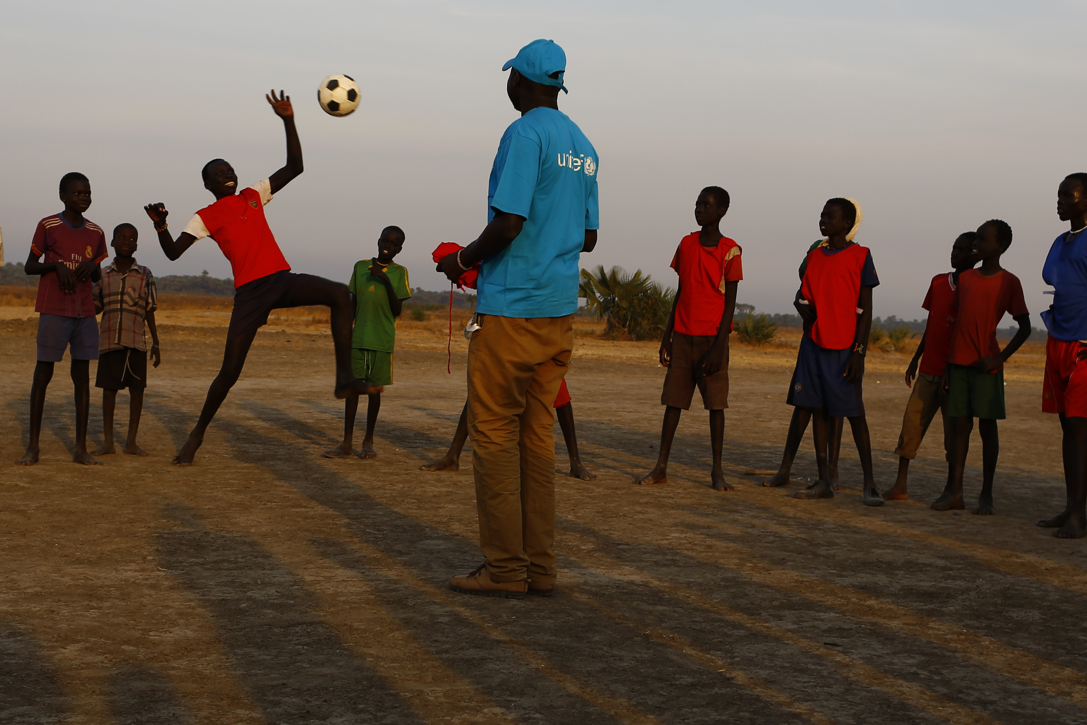 Children standing in a circle watch as a child kicks a football in the air, as a man in a UNICEF t-shirt in the middle looks on.