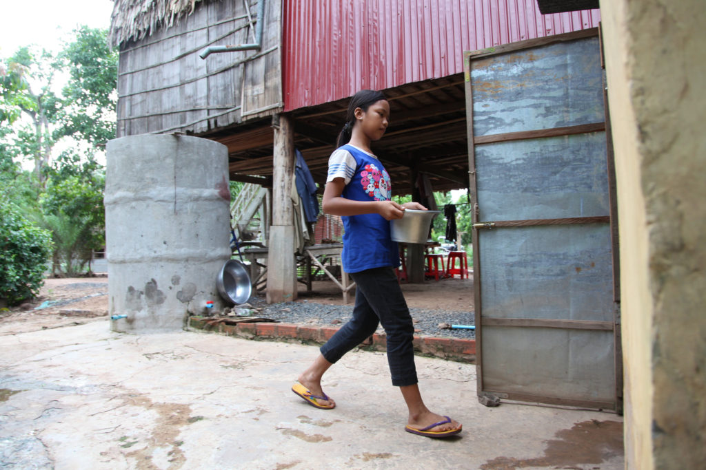 A girl walks carrying a metal container.