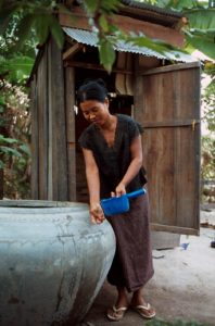Woman tilting a water container over her hands