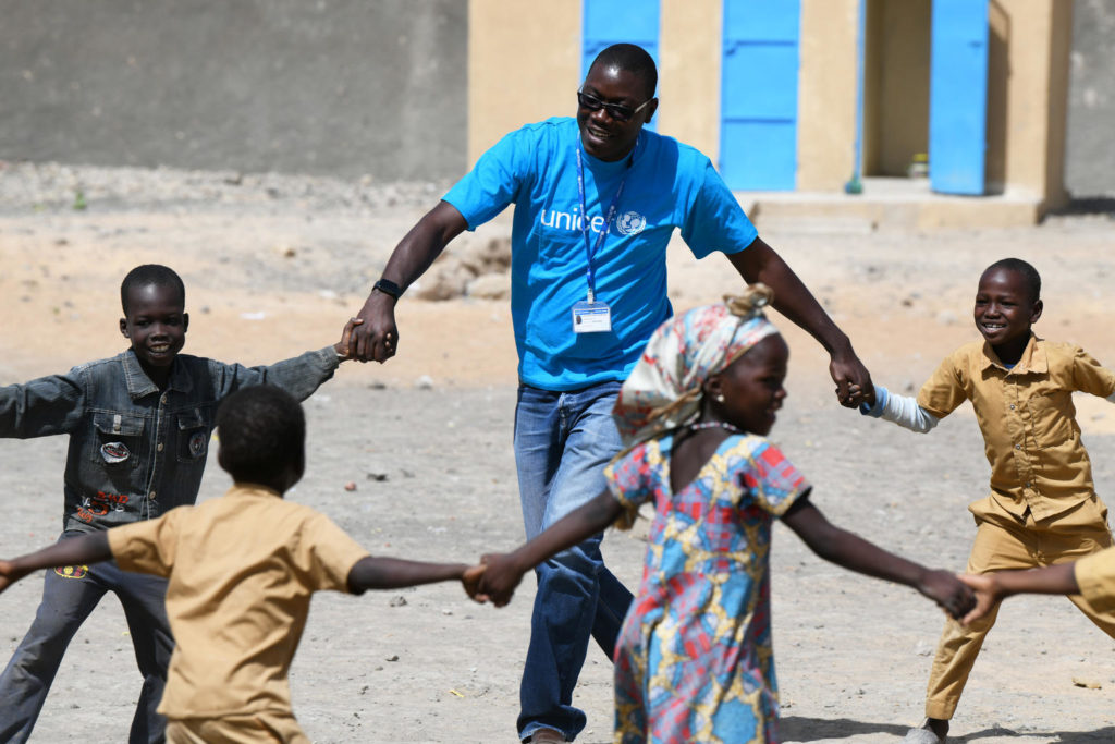 A man in a blue UNICEF tee plays outdoors along with some children