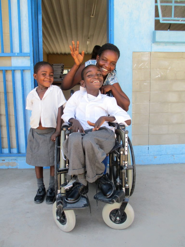 A child in school uniform sits on a wheelchair and smiles while a girl also in uniform and a lady standing around him.
