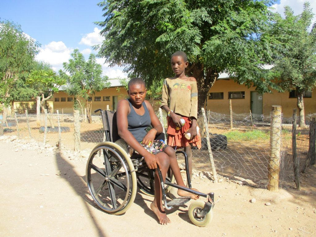 A girl sitting on a wheelchair as a boy stands besides her.