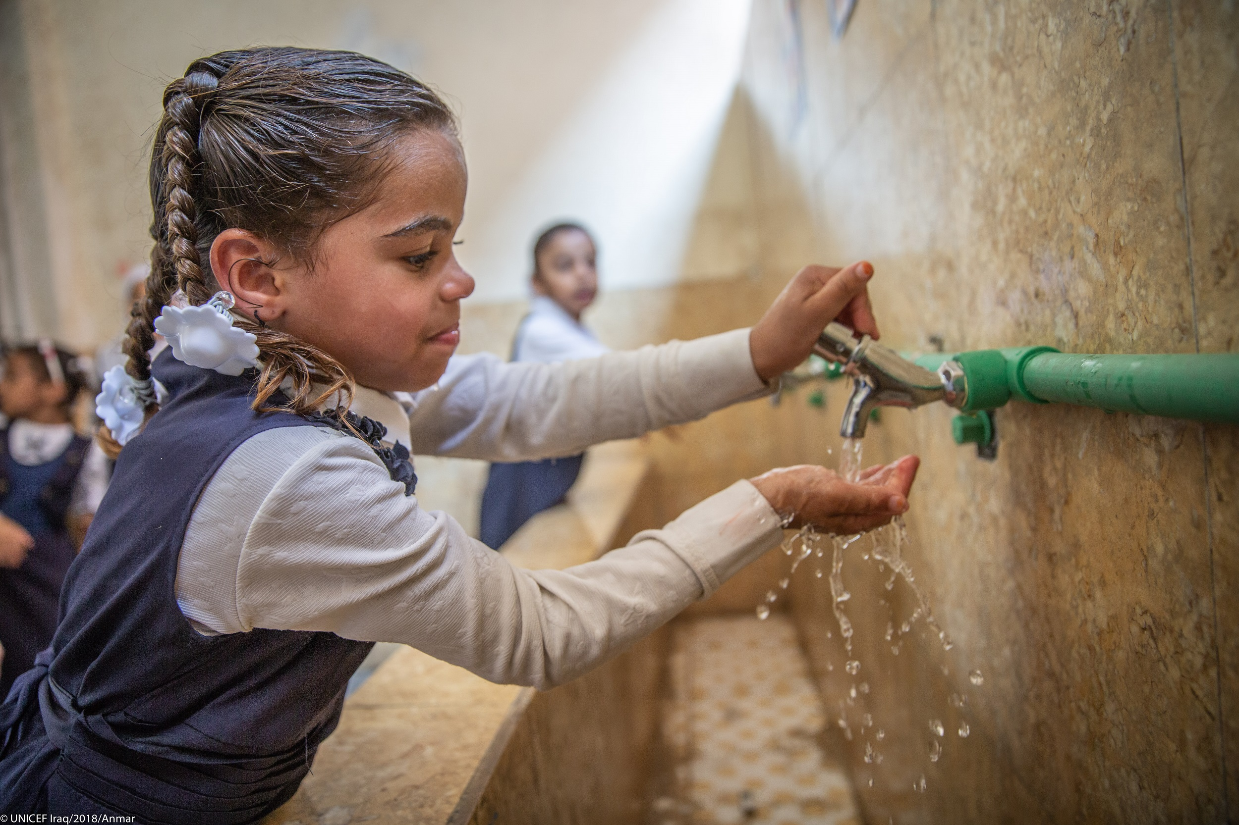 A school girl collects water in her hands from a communal water tap.
