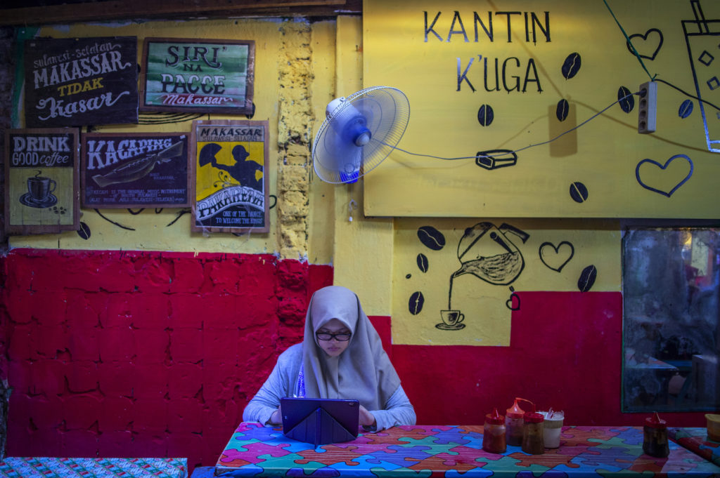 A girl wearing a traditional headscarf sits working on a tablet PC with a wall behind her with signs, posters and quotes