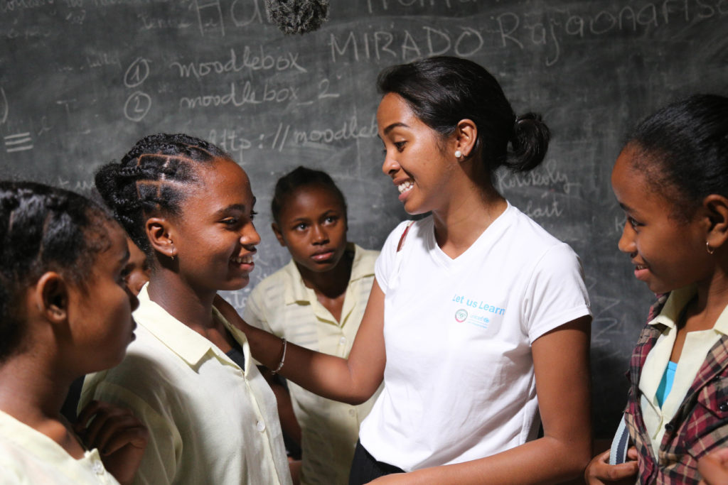 A group of girls in conversation in a classroom.