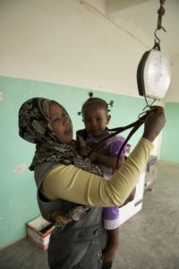 A lady holding a child strapped to a weighing machine