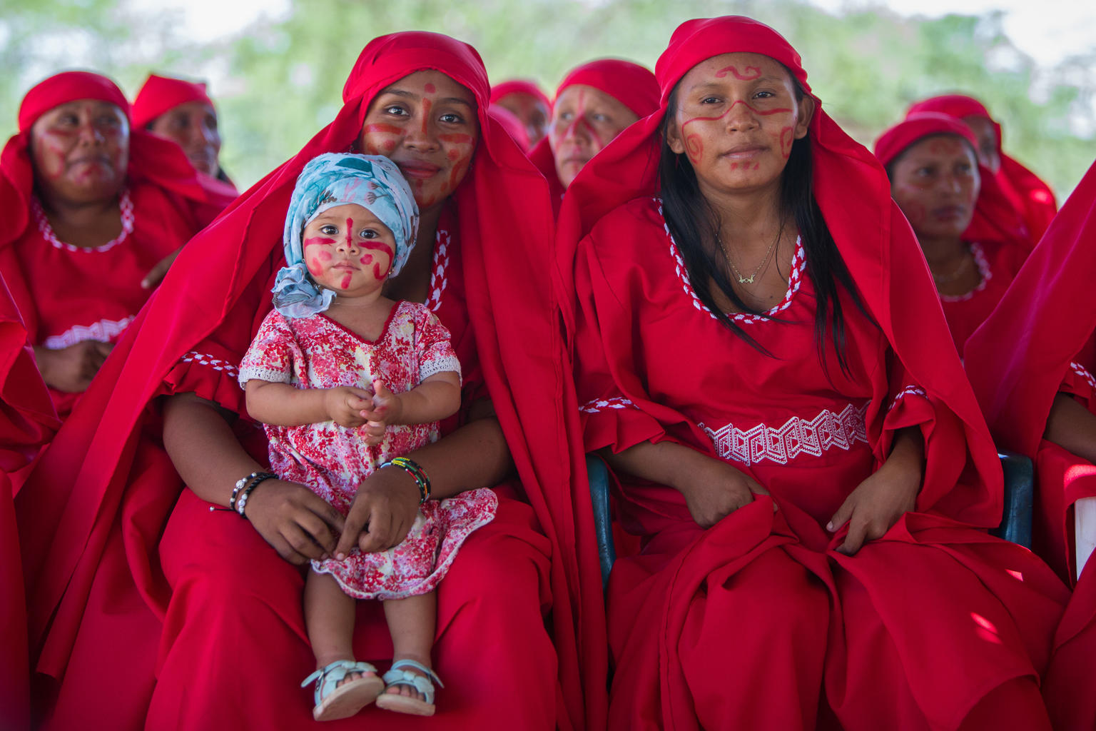 Women in traditional red attire and red face paint. One of them holds an infant girl also in face paint.