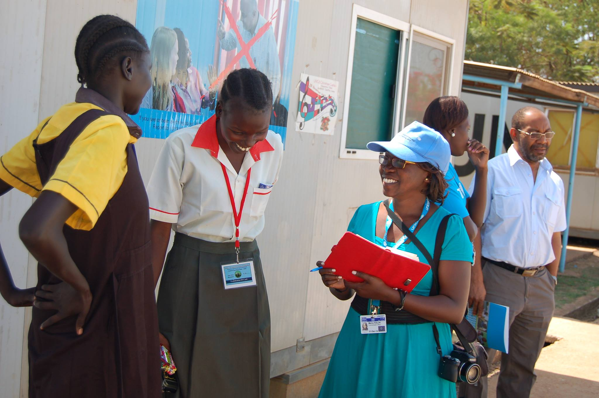 A woman in a blue hat talking to a pair of girl school students