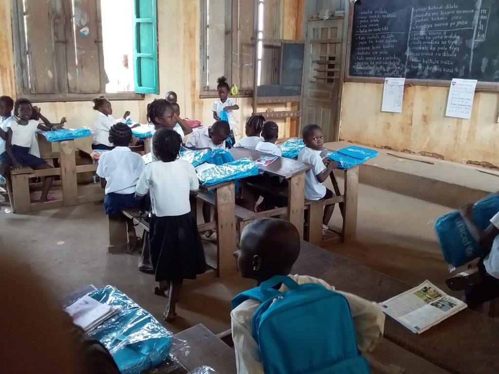 School children in a classroom with school bags in their plastic covering