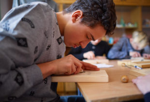 A boy carves on wood.