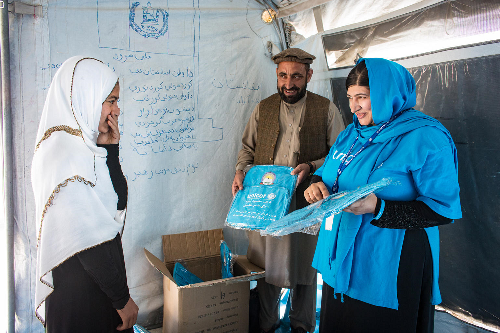 A lady hands out blue school bags from a cardboard box. A smiling girl stands opposite her.