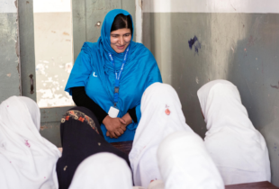 A lady in a blue tradiotional headscarf addresses school girls in a classroom