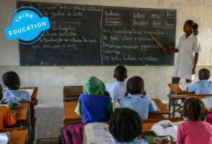 A teacher pointing at the blackboard oin a classroom full of students