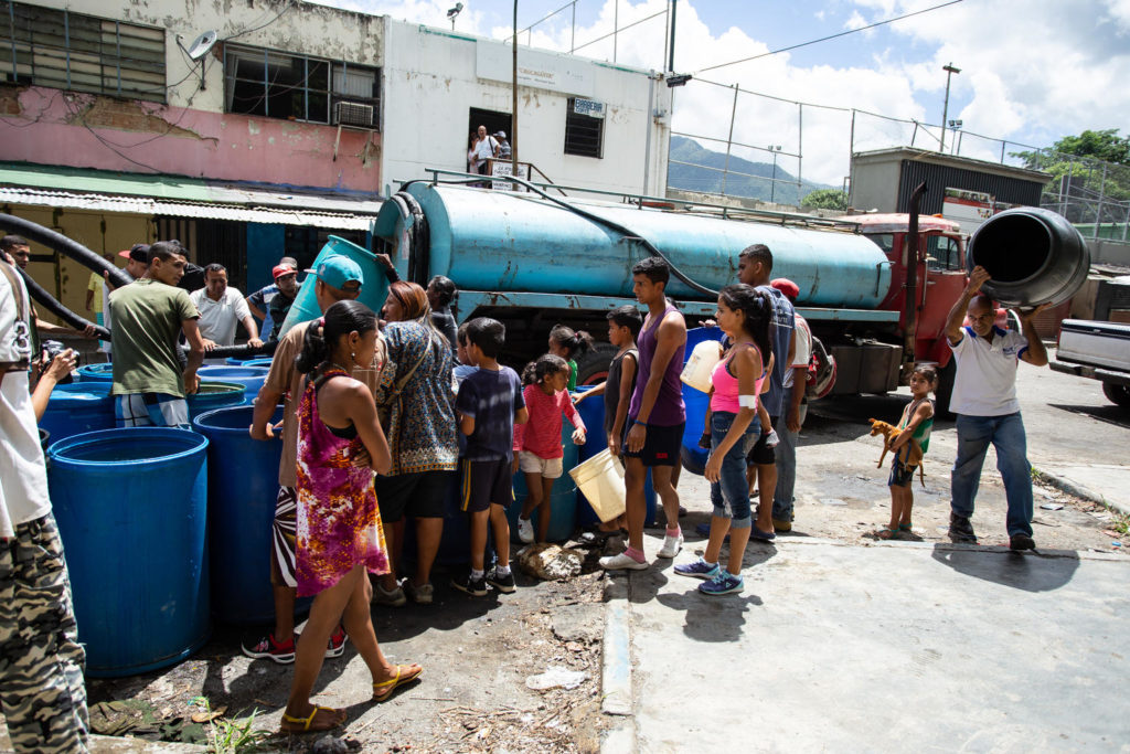 A group of people gathered around a water taker