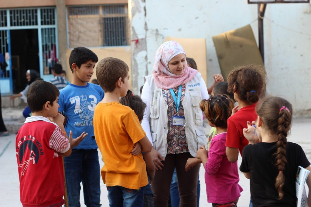A lady talking to some children on the street