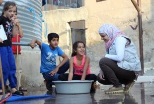 A woman squats alongside some children beside a clean water storage tank.