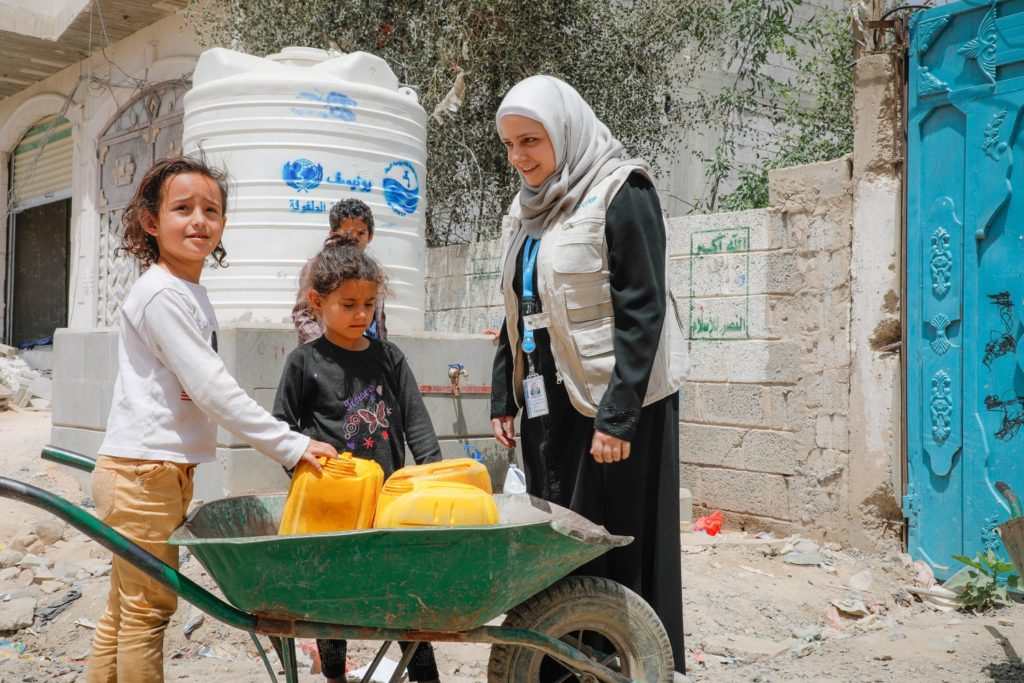 A woman stands alongside some children next to a wheelbarrow filled with jerrycans.