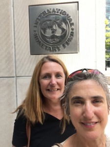 Two UNICEF staffers in front of a plaque on the wall behind them that reads 'International Monetary Fund'.