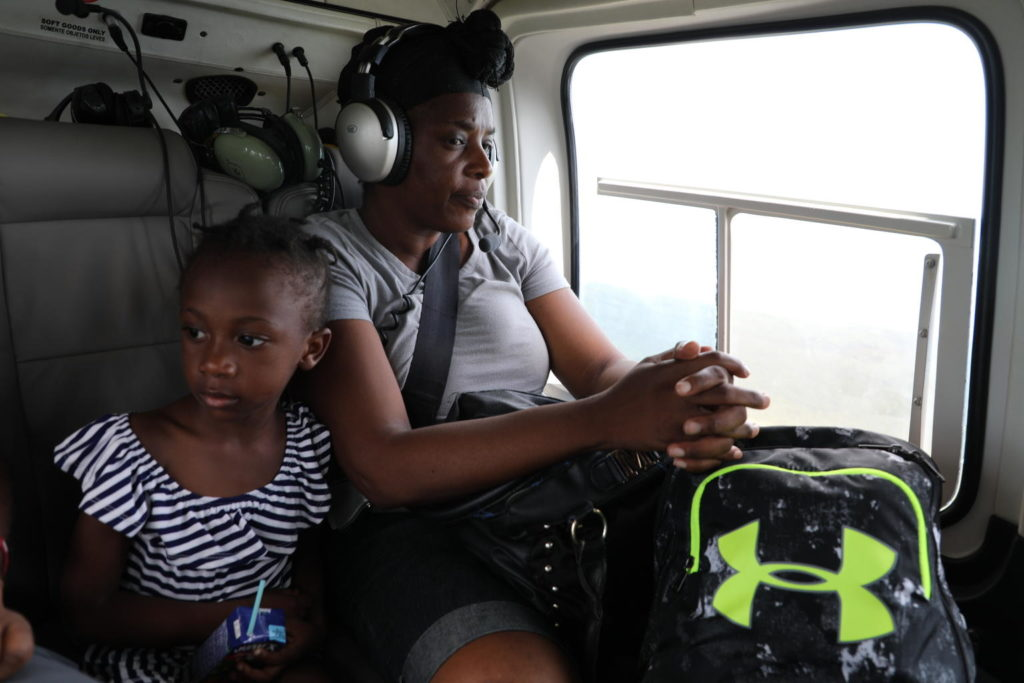 A mom and her daughter in a helicopter seat.